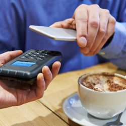 Man Using Contactless Payment App On Mobile Phone In Cafe