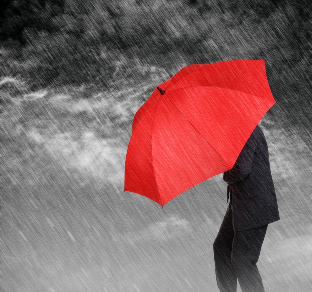 Businessman with red umbrella protecting himself from the storm concept for protection from recession or economic depression etc