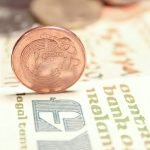 Old Irish penny on edge on top of an old Irish pound note (punt) with blurred Irish coins in background
