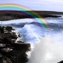 cliffs and coastline of the burren in county clare ireland with waves crashing on the rocks causing rainbow
