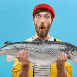Indoor shot of astonished bearded fisherman dressed casually holding huge fish looking at camera with bugged eyes and jaw dropped being shocked to catch such big trout or salmon. Surprisment