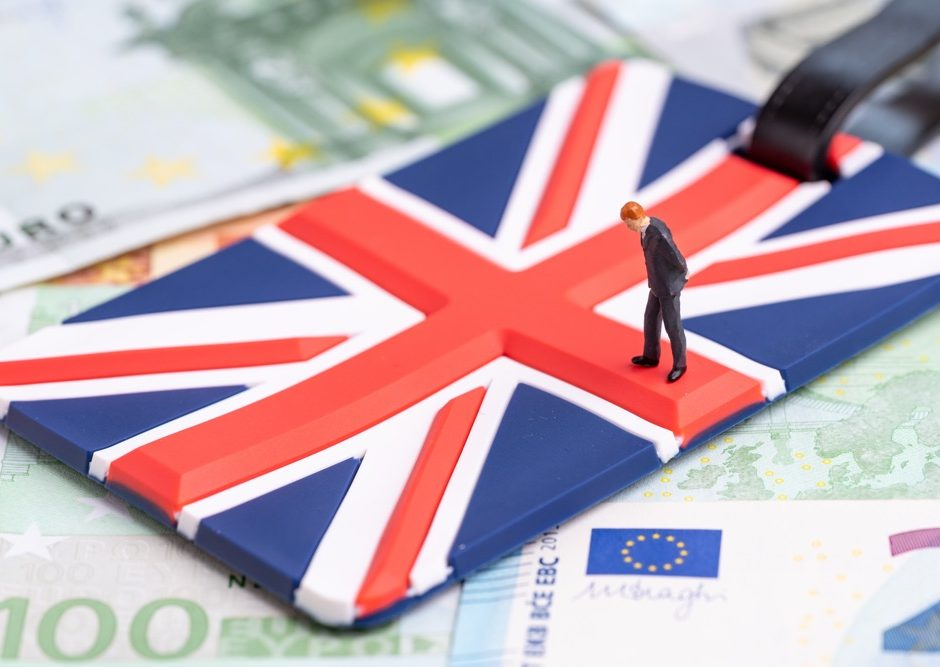 Europe, Brexit or Britain economy or financial concept, miniature figure businessman country leader standing on Union Jack UK national flag on pile of Euro banknotes money.