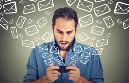 Closeup portrait young shocked man busy sending messages emails from smart phone email icons flying of mobile phone isolated on gray wall background. Telecommunications, internet, data plan concept