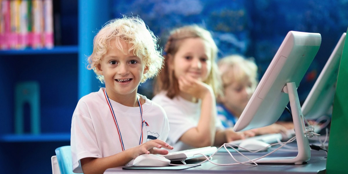Kids with computer. Children learning and studying information and communications technology using personal computers in school class or library. Student at pc. Modern education device for child.