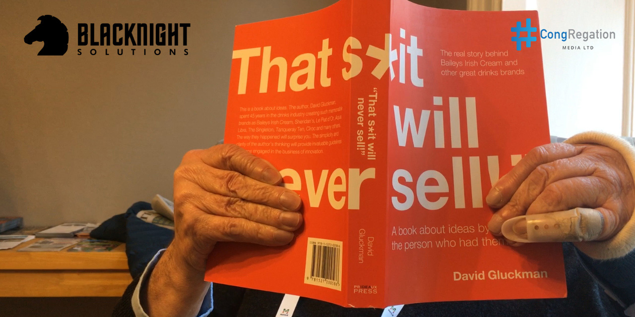 "David Gluckman shows the cover of his book ""That S*it will Never Sell"" at Congregation in 2017"
