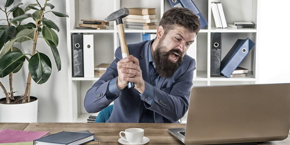 Man attacking computer with hammer